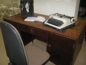 Ant pirmo poeto darbo stalo - mylimos žmonos Genovaitės nuotrauka ir spausdinimo mašinėlė, kuria Justinas Marcinkevičius atspausdino didžiąją dalį savo kūrinių.